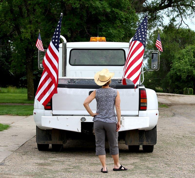 Una mujer que mira las banderas americanas exhibidas en una camioneta pickup foto de archivo