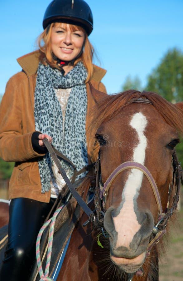 Una mujer que monta un caballo fotografía de archivo libre de regalías