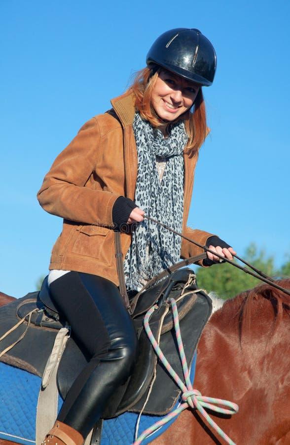 Una mujer que monta un caballo foto de archivo libre de regalías