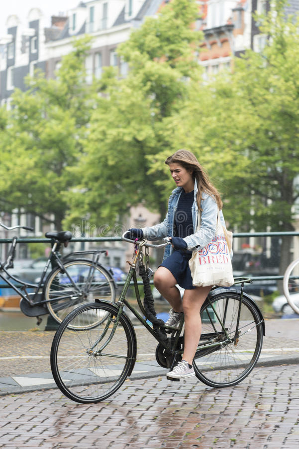 Una mujer que monta una bici fotografía de archivo libre de regalías