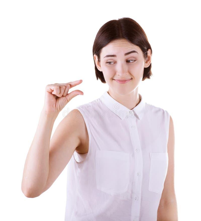 Una mujer que muestra con su mano algo pequeño Una muchacha escéptica aislada en un fondo blanco Una señora morena sarcástica fotografía de archivo