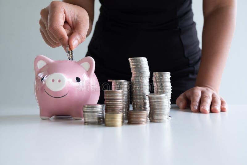 Una mujer que pone la moneda en la hucha rosada con la pila de las monedas imágenes de archivo libres de regalías