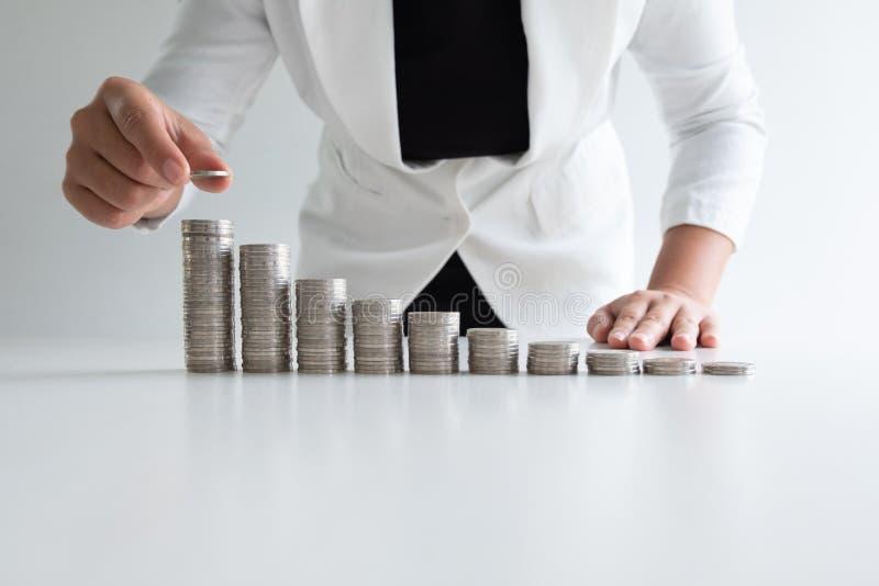 Una mujer que pone la moneda en monedas del crecimiento representa gráficamente en el traje blanco foto de archivo libre de regalías