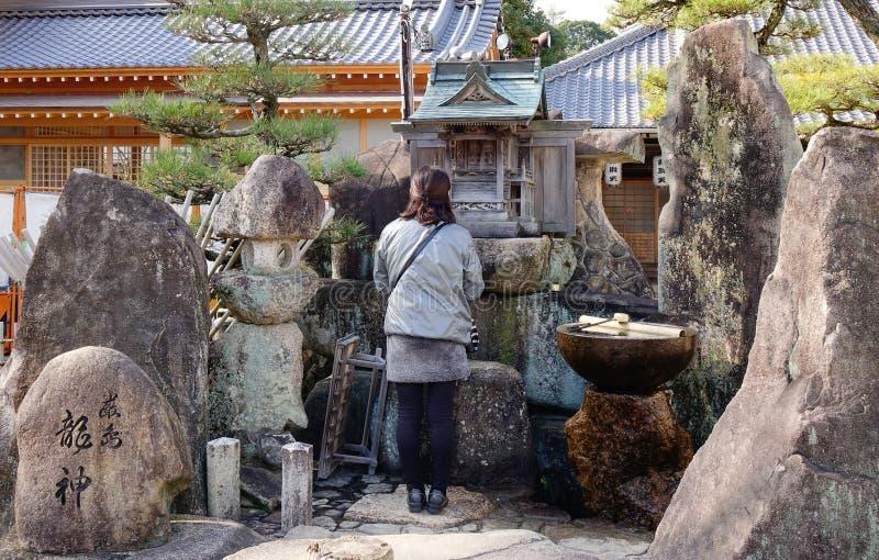 Una mujer que ruega en la capilla de Itsukushima en Hiroshima, Japón fotos de archivo libres de regalías