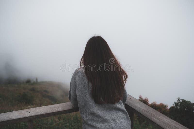Una mujer que se coloca solamente en el balcón que mira de niebla blanco y las montañas fotografía de archivo