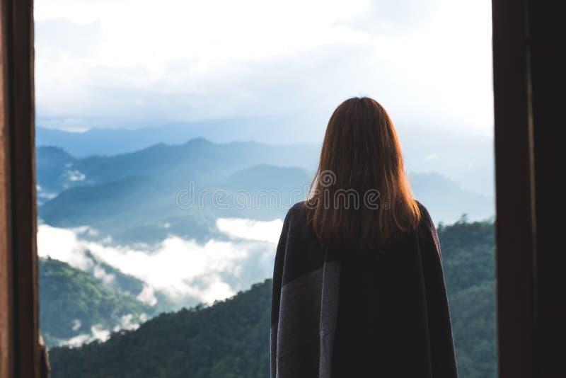 Una mujer que se coloca solamente en el balcón que mira las montañas en día de niebla con el fondo del cielo azul imagen de archivo libre de regalías