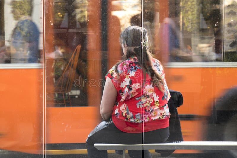 Una mujer que se sienta en esperar de la parada de autobús imagenes de archivo
