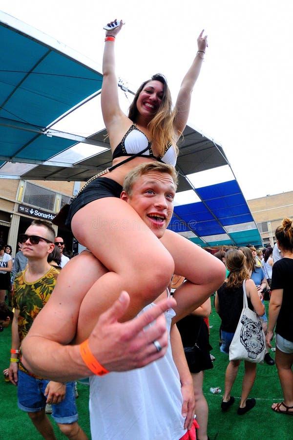 Una mujer que se sienta en los hombros de su novio en el festival del sonar imagen de archivo libre de regalías