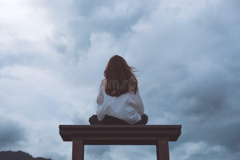Una mujer que se sienta solamente en un banco de madera en el parque con el cielo nublado y melancólico fotos de archivo libres de regalías