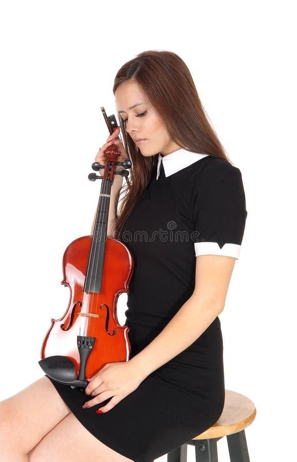 Una mujer que sienta y que sostiene su violín, descansando fotografía de archivo