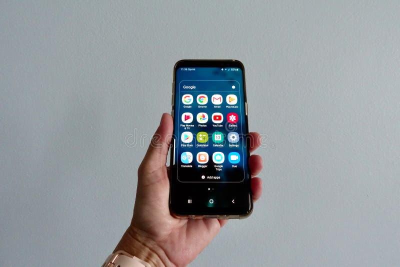 Una mujer que sostenía un teléfono de Samsung con los apps de Google exhibió imagen de archivo