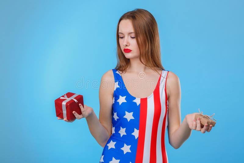 Una mujer que sostiene dos pequeñas cajas de regalo en ambas manos En un fondo azul imagen de archivo libre de regalías