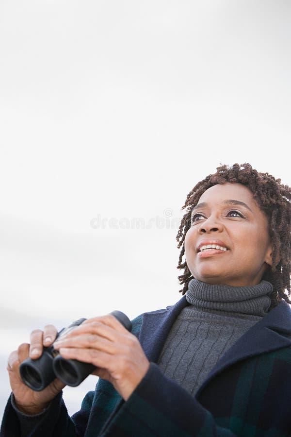 Una mujer que sostiene los prismáticos fotografía de archivo libre de regalías