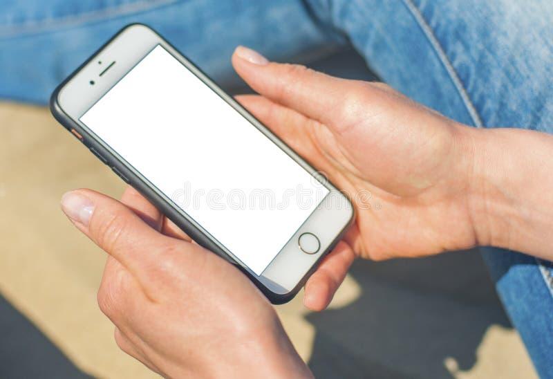 Una mujer que sostiene un tel?fono m?vil blanco con una pantalla en blanco imagen de archivo