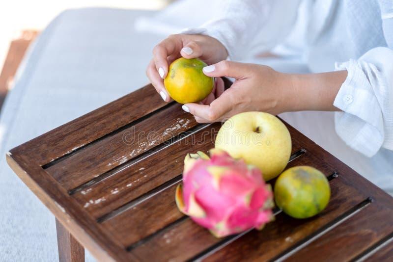 Una mujer que sostiene y que pela una naranja para comer con la pera y la fruta del dragón en una tabla fotos de archivo
