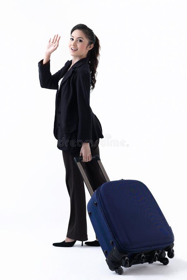 Una mujer que tira de un equipaje y que agita la mano foto de archivo libre de regalías
