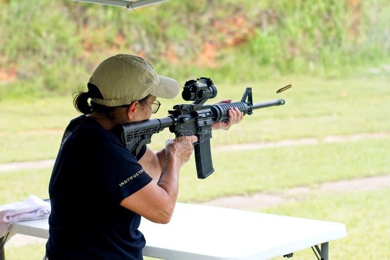 Una mujer que tira un rifle AR-15 foto de archivo