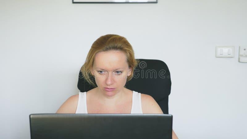 Una mujer que usa su ordenador portátil, sentándose en la tabla, enojado e irritado, jura Emociones humanas Concepto del apego de fotografía de archivo