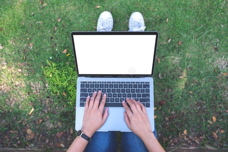 Una mujer que usa y mecanografiando en el ordenador portátil con la taza blanca en blanco de la pantalla y de café en la tabla en fotografía de archivo