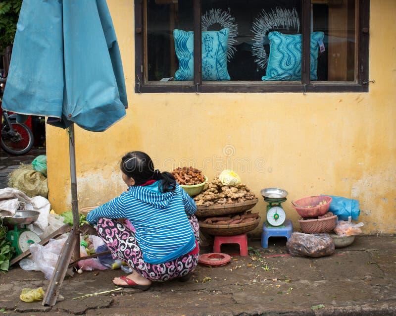 Una mujer que vende las frutas en el mercado local en Hoi An, Vietnam foto de archivo