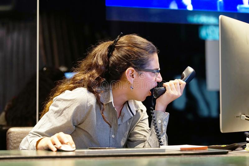 Una mujer-recepción jura con el cliente por el teléfono imagenes de archivo