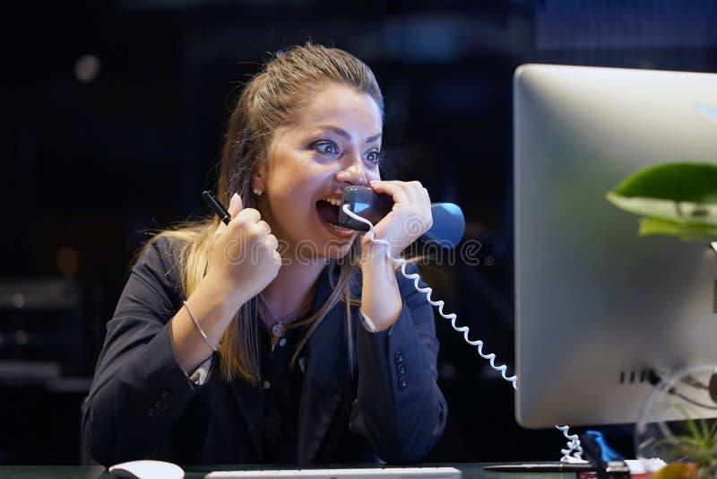 Una mujer-recepción jura con el cliente por el teléfono foto de archivo libre de regalías