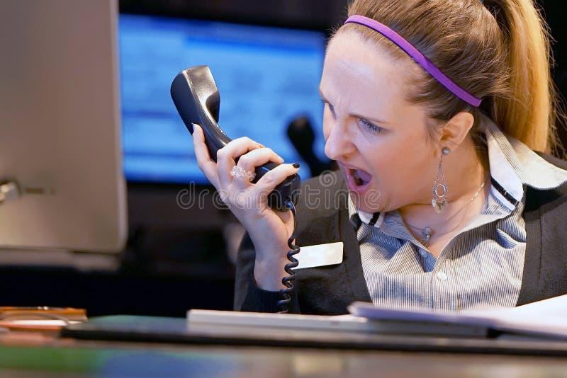 Una mujer-recepción jura con el cliente por el teléfono imagen de archivo
