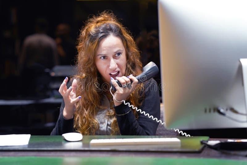 Una mujer-recepci?n jura con el cliente por el tel?fono imágenes de archivo libres de regalías