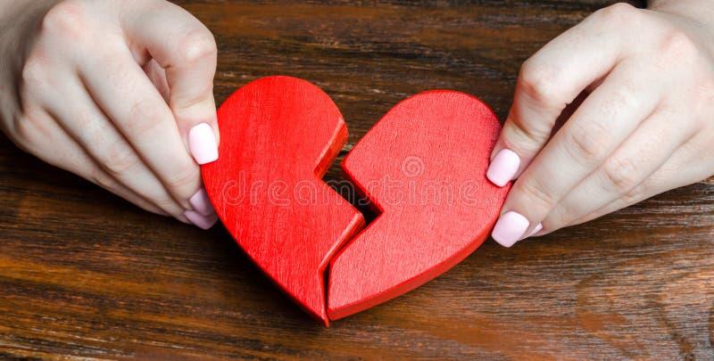Una mujer recoge un corazón quebrado en sus manos Concepto de amor y de relaciones Servicios del psicoterapeuta de la familia rec fotos de archivo libres de regalías