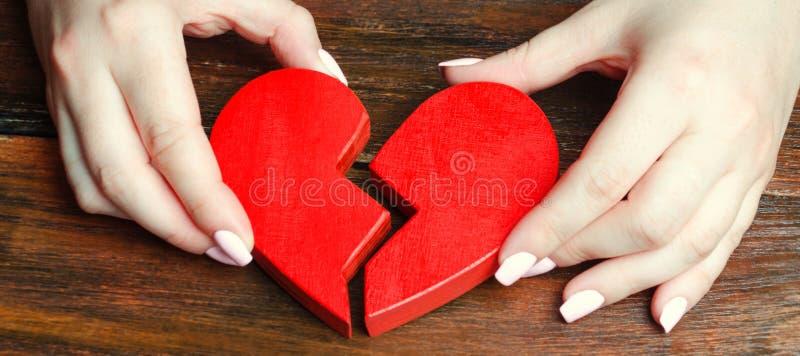 Una mujer recoge un corazón quebrado en sus manos Concepto de amor y de relaciones Servicios del psicoterapeuta de la familia rec fotografía de archivo