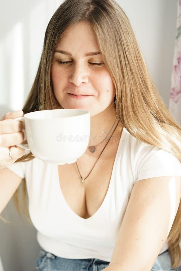 Una mujer rubia de pelo largo joven en una camiseta blanca está bebiendo té foto de archivo libre de regalías