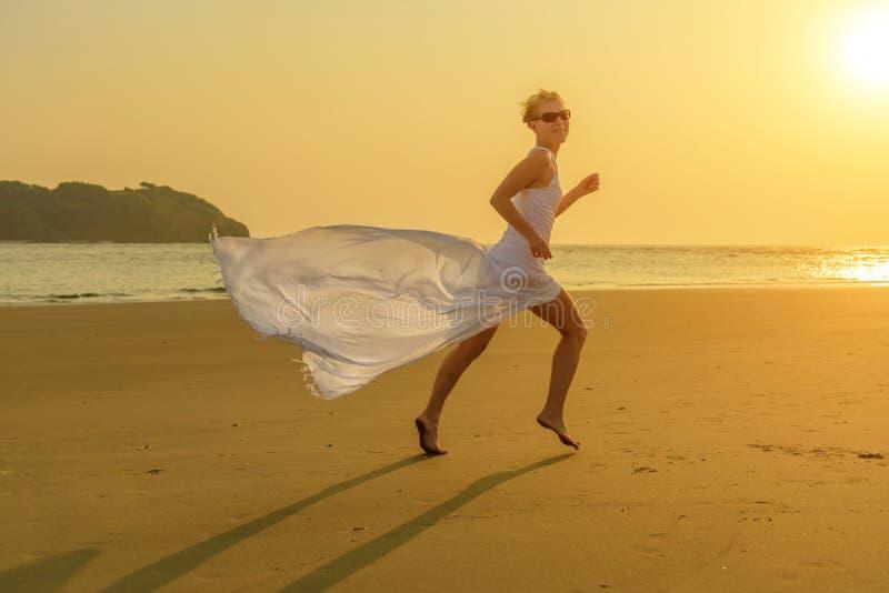 Una mujer rubia del caucásico joven feliz en gafas de sol y funcionamientos blancos de un vestido que agitan abajo de la playa en imagen de archivo