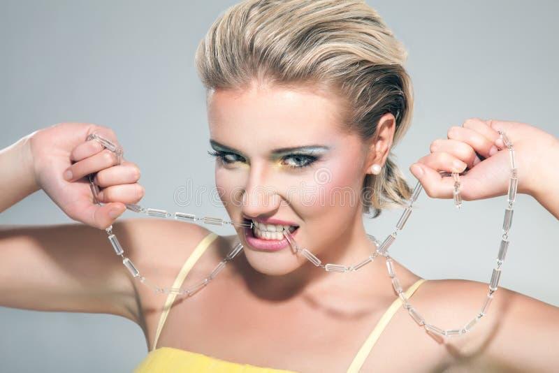 Una mujer rubia joven hermosa que muerde un collar imagen de archivo libre de regalías