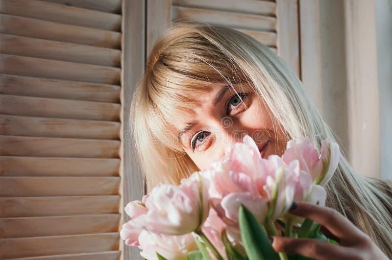 Una mujer rubia joven que sostiene las flores por la ventana, sonriendo foto de archivo