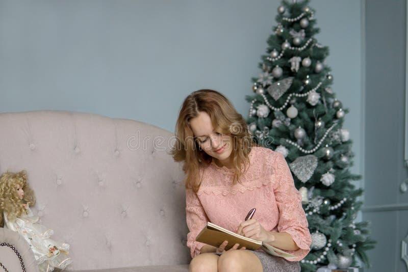 Una mujer rubia joven se sienta en un sofá gris en una blusa rosada y escribe con su mano izquierda con una pluma en un cuaderno  imagen de archivo