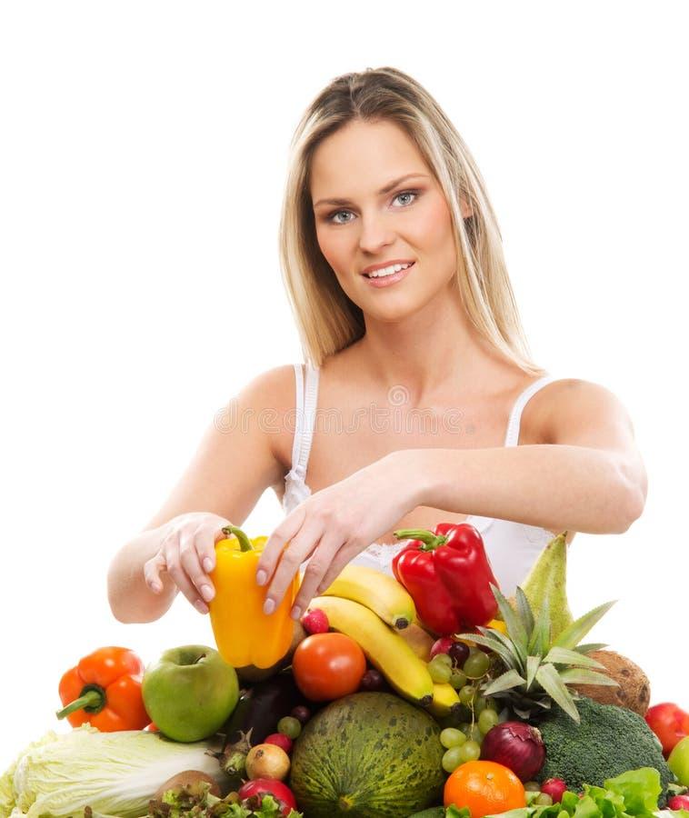 Una mujer rubia joven y una pila de frutas frescas fotografía de archivo