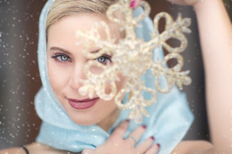 Una mujer rubia magnífica con una bufanda azul que sostiene un copo de nieve del oro delante de su cara en la nieve imágenes de archivo libres de regalías