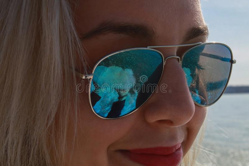 Una mujer rubia sonríe en un par de gafas de sol azules fotos de archivo