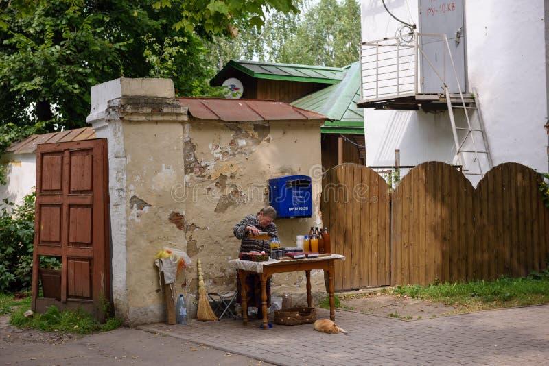 Una mujer rusa mayor que vende las botellas de aguamiel, tarros con el atasco y el  de Ñ sube de bayas Suzdal, Rusia imágenes de archivo libres de regalías