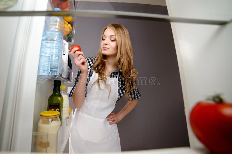 Una mujer saca un tomate del refrigerador foto de archivo