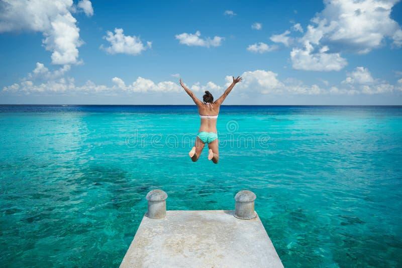 Una mujer salta en agua azul fotos de archivo