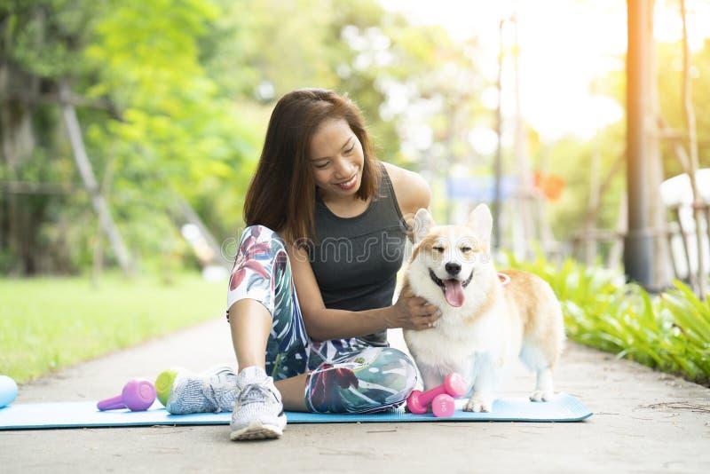 Una mujer sana que juega con un perrito del corgi mientras que ejercita fotografía de archivo libre de regalías