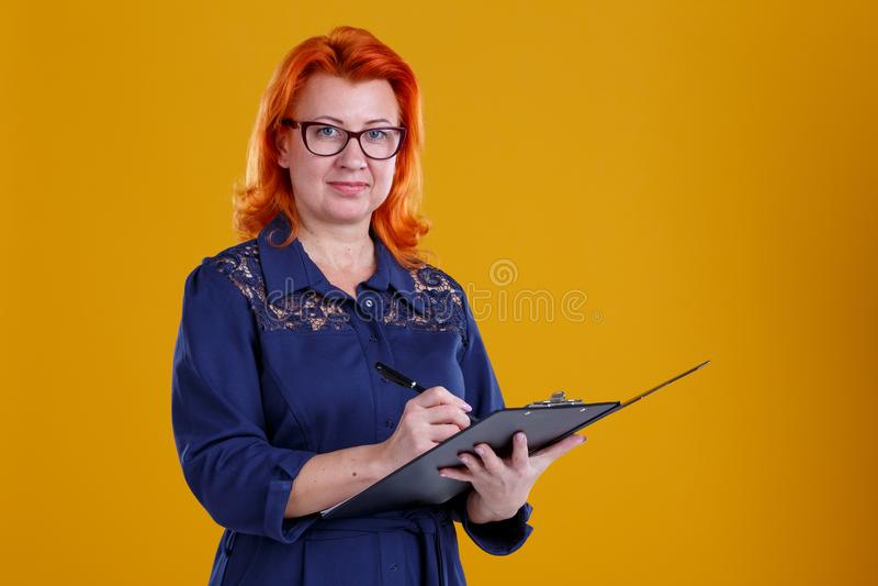 Una mujer se coloca con una tableta que hace notas en un fondo amarillo fotos de archivo