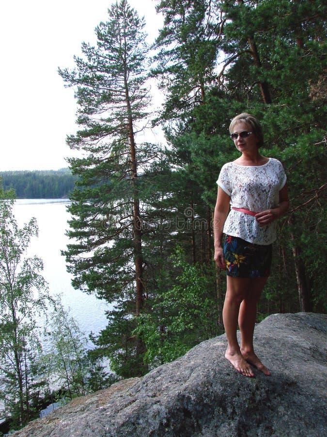 Una mujer se coloca en una roca fotos de archivo libres de regalías