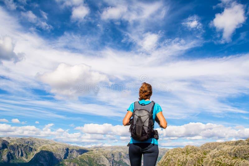 Una mujer se está colocando al borde del acantilado en la manera al canto rodado fotografía de archivo libre de regalías