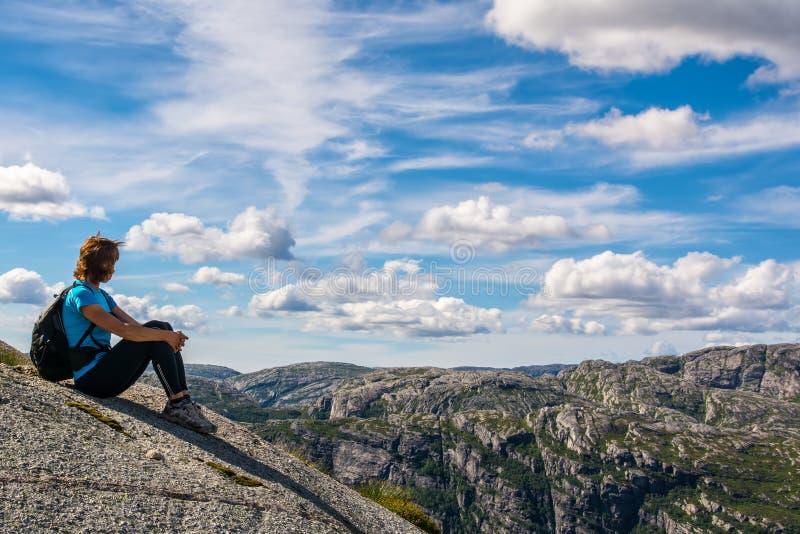 Una mujer se está sentando al borde del acantilado en la manera al canto rodado K imágenes de archivo libres de regalías