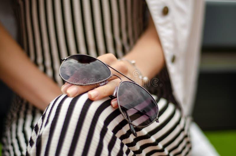 Una mujer se está sentando en un banco con las gafas de sol en naturaleza del sol de las manos imagenes de archivo
