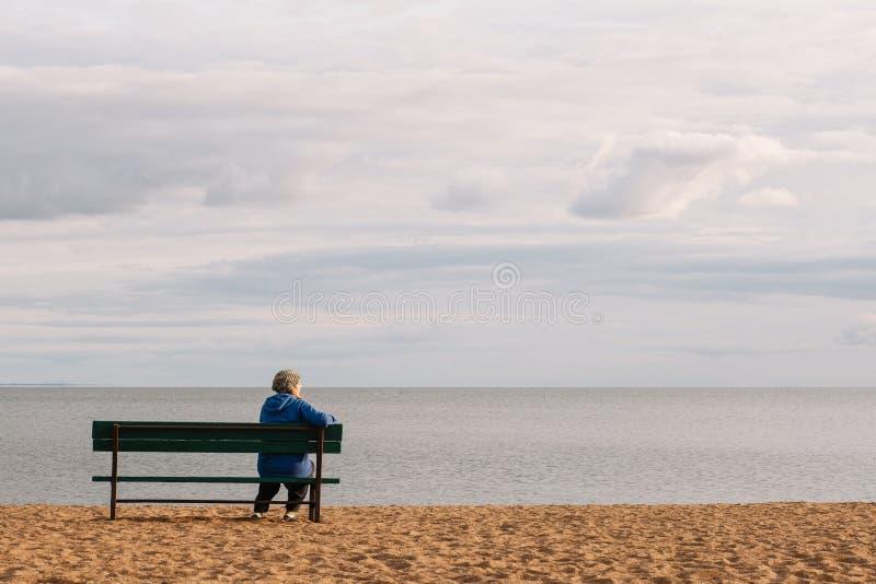 Una mujer se sienta solamente en un banco en los rayos del sol poniente Muchacha atractiva que se sienta en un banco de madera co fotografía de archivo libre de regalías