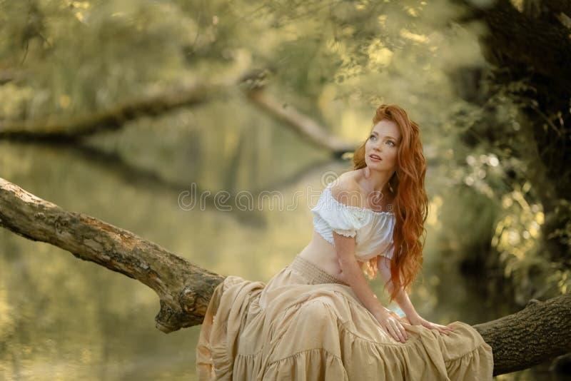 Una mujer sentada en una rama de árbol bajada sobre el río imagenes de archivo