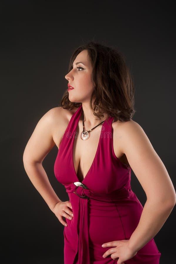 Una mujer sexy bruneada con vestido rojo foto de archivo